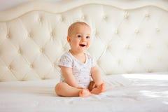 Beau bébé garçon dans la chambre à coucher ensoleillée blanche Photographie stock