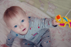 Beau bébé garçon s'asseyant et plaing avec le jouet de mobile de huche photos libres de droits