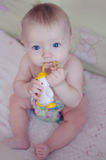 Beau bébé garçon s'asseyant et suçant sur son jouet photo stock