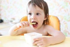 Beau bébé mangeant de la purée fruitée seul Image stock