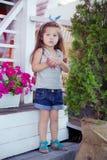Beau bébé mignon élégant avec des cheveux de brune posant sur le jardin en bois complètement des fleurs portant les chemises minu Image libre de droits