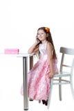 Beau bébé parlant au téléphone dans une robe d'isolement sur un fond blanc photographie stock libre de droits