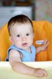 Beau bébé s'asseyant sur la chaise de bébé Photographie stock libre de droits