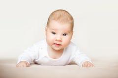 Beau bébé se trouvant sur son estomac dans le lit Photographie stock libre de droits