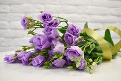 Beau bel eustoma lilas avec un ruban de satin sur la table blanche photos stock