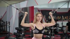 Beau biceps sportif de trains de jeune fille sur un simulateur de simulateur de bloc dans le gymnase banque de vidéos