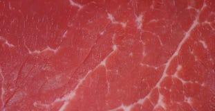 Beau bifteck juteux de viande fraîche sur une table avec du sel, le romarin, l'ail, et la tomate sur un fond noir, vue supérieure Photographie stock libre de droits