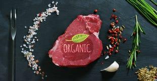 Beau bifteck juteux de viande fraîche sur une table avec du sel, le romarin, l'ail, et la tomate sur un fond noir, vue supérieure Images stock