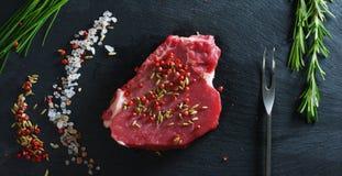 Beau bifteck juteux de viande fraîche sur une table avec du sel, le romarin, l'ail, et la tomate sur un fond noir, vue supérieure Photo libre de droits