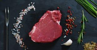 Beau bifteck juteux de viande fraîche sur une table avec du sel, le romarin, l'ail, et la tomate sur un fond noir, vue supérieure Images libres de droits