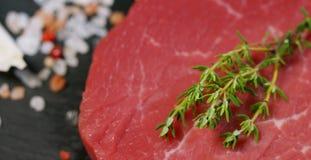 Beau bifteck juteux de viande fraîche sur une table avec du sel, le romarin, l'ail, et la tomate sur un fond noir, vue supérieure Photos stock