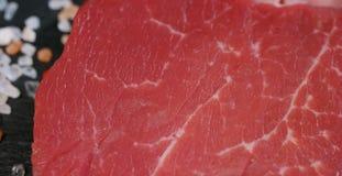 Beau bifteck juteux de viande fraîche sur une table avec du sel, le romarin, l'ail, et la tomate sur un fond noir, vue supérieure Image libre de droits