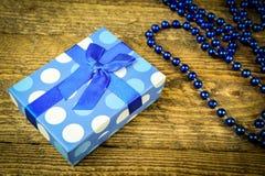 Beau bleu un présent avec les perles bleues sur un fond en bois Images libres de droits