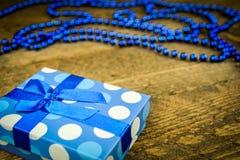 Beau bleu un présent avec les perles bleues sur un fond en bois Image libre de droits