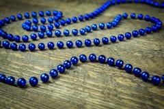 Beau bleu un présent avec les perles bleues sur un fond en bois Photographie stock libre de droits