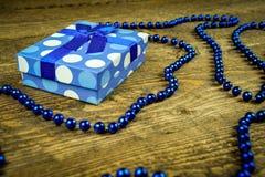Beau bleu un présent avec les perles bleues sur un fond en bois Image stock