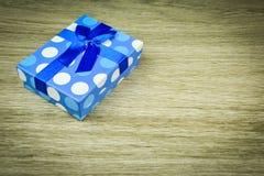 Beau bleu un présent avec les perles bleues sur un fond en bois Photo libre de droits