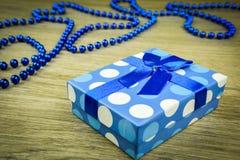 Beau bleu un présent avec les perles bleues sur un fond en bois Images stock