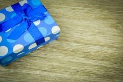 Beau bleu un présent avec les perles bleues sur un fond en bois Photographie stock
