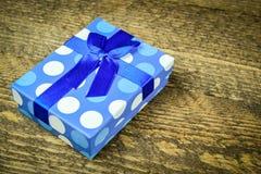 Beau bleu un présent avec les perles bleues sur un fond en bois Photos stock