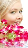 Beau blond avec l'orchidée dans l'eau Photo libre de droits