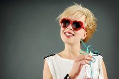 Beau blond avec les lunettes de soleil rouges Photos stock