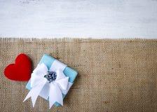 Beau boîte-cadeau avec le coeur rouge sur le tissu hessois avec l'espace sur le fond en bois blanc de texture Image stock