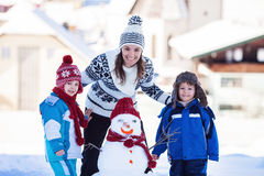 Beau bonhomme de neige heureux de fondation d'une famille dans le jardin, horaire d'hiver, Image libre de droits