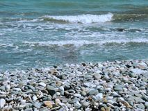 Beau bord de la mer avec des vagues et des pierres colorées images stock
