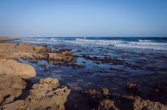 Beau bord de la mer rocheux abandonné de paysage, vagues bleues photo libre de droits