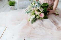 Beau bouquet élégant des roses et de la verdure dans les mains douces de la belle fille de jeune mariée dans une robe rose l'air Photo libre de droits