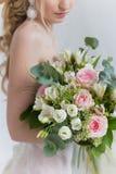 Beau bouquet élégant des roses et de la verdure dans les mains douces de la belle fille de jeune mariée dans une robe rose l'air Photo stock