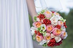 Beau bouquet coloré de mariage dans une main d'une jeune mariée Photo libre de droits
