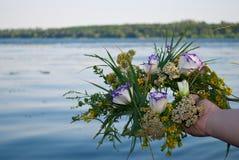 Beau bouquet d'une guirlande des wildflowers une fille tenant une rivière au-dessus de l'eau images stock