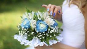Beau bouquet de différentes couleurs dans les mains de la jeune mariée dans une robe blanche Mariée dans la robe blanche avec le  Photo stock