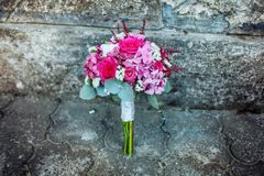 Beau bouquet de mariage avec les roses et les baies roses sur le fond en pierre photographie stock libre de droits