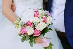 Beau bouquet de mariage des fleurs dans des mains de la jeune mariée Photographie stock libre de droits