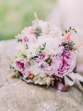 Beau bouquet de mariage des pivoines colorées avec des herbes placées sur la fontaine Photographie stock