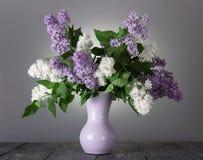 Beau bouquet des fleurs blanches et lilas dans le vase sur le gris photographie stock libre de droits