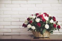 Beau bouquet des roses et d'un panier en bois Photographie stock