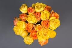 Beau bouquet des roses oranges et jaunes au-dessus du gris Photo stock