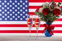 Beau bouquet, drapeau américain et verres de champagne Photographie stock