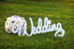 Beau bouquet et un mariage en bois blanc de signe sur l'herbe Photographie stock