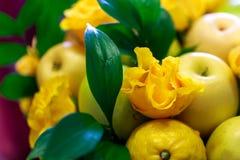 Beau bouquet fait main se composant des pommes jaunes et vertes, des citrons, des feuilles de vert et des roses jaunes Image libre de droits