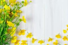 Beau bouquet jaune de renoncule se trouvant sur les conseils en bois blancs Photographie stock libre de droits