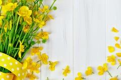 Beau bouquet jaune de renoncule se trouvant sur les conseils en bois blancs Photos stock