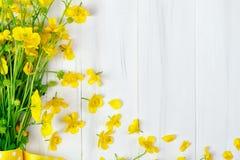 Beau bouquet jaune de renoncule se trouvant sur les conseils en bois blancs Photo libre de droits