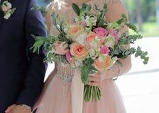 Beau bouquet nuptiale dans des mains de la jeune mariée Bouquet de mariage des roses de pêche par David Austin, aqua tête simple  Photo libre de droits
