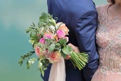 Beau bouquet nuptiale dans des mains de la jeune mariée Bouquet de mariage des roses de pêche par David Austin, aqua tête simple  Images stock