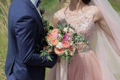 Beau bouquet nuptiale dans des mains de la jeune mariée Bouquet de mariage des roses de pêche par David Austin, aqua tête simple  Image libre de droits
